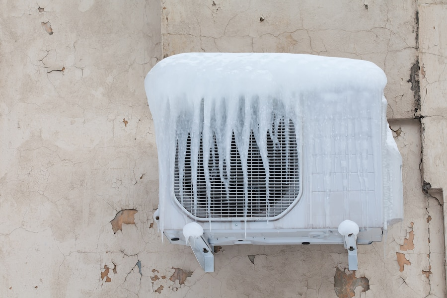 Air conditioner with frozen ice and icicles. Cooling, cold temperature concept image. Aged wall background.