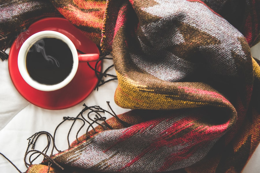 Cozy winter home background, cup of hot coffee with marshmallow, warm knitted sweater on white bed background, vintage tone. Lifestyle concept.