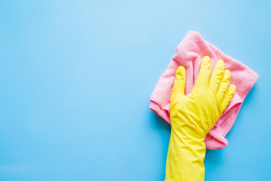 Yellow gloved hand cleaning dust off of a blue wall with a pink rag in San Marcos, Texas.