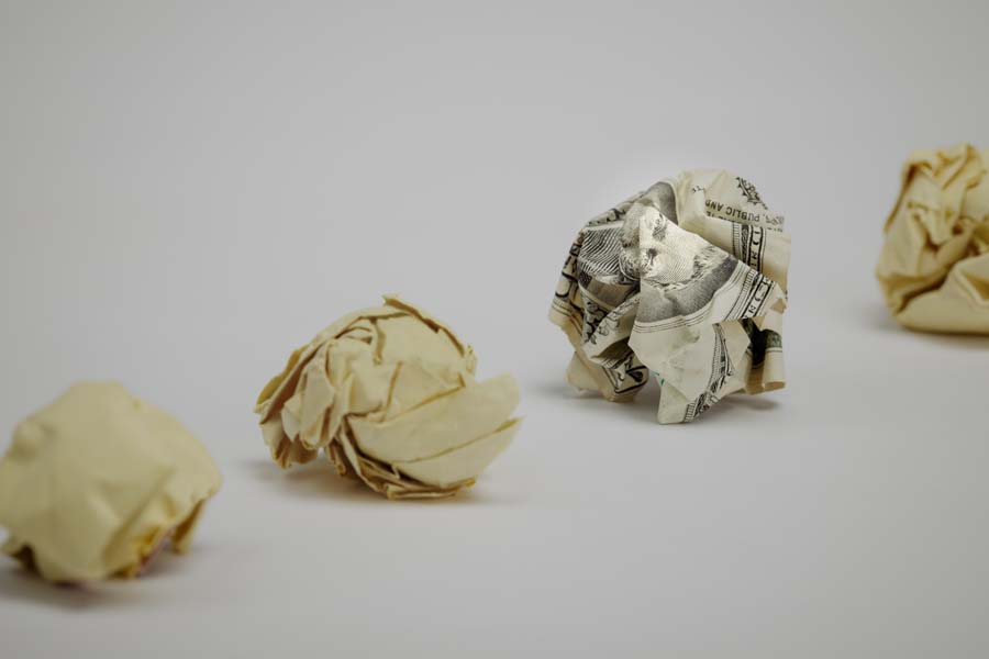 Crumpled dollar bill among office paper.