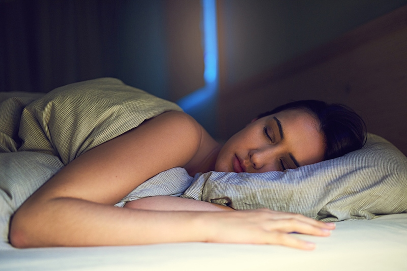 Shot of a young woman sound asleep in her bedroom air conditioning ac sleep benefits
